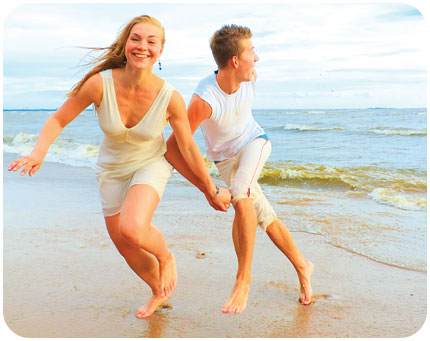 a young couple frolic barfoot on the beach on a sunny day