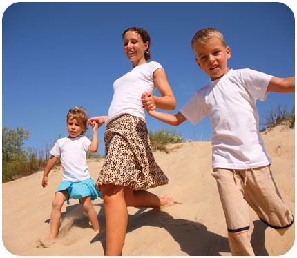 A boy and girl run bare foot down and sand dune with their mother
