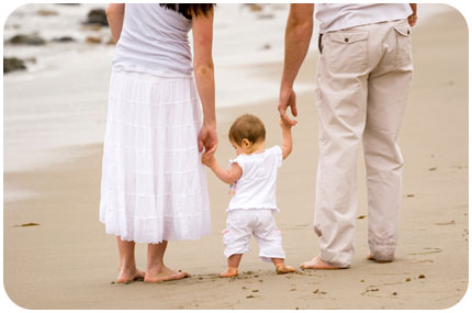 a toddler walks barefoot on a beach holding his parents hands